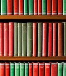 Three rows of green and red books on shelves