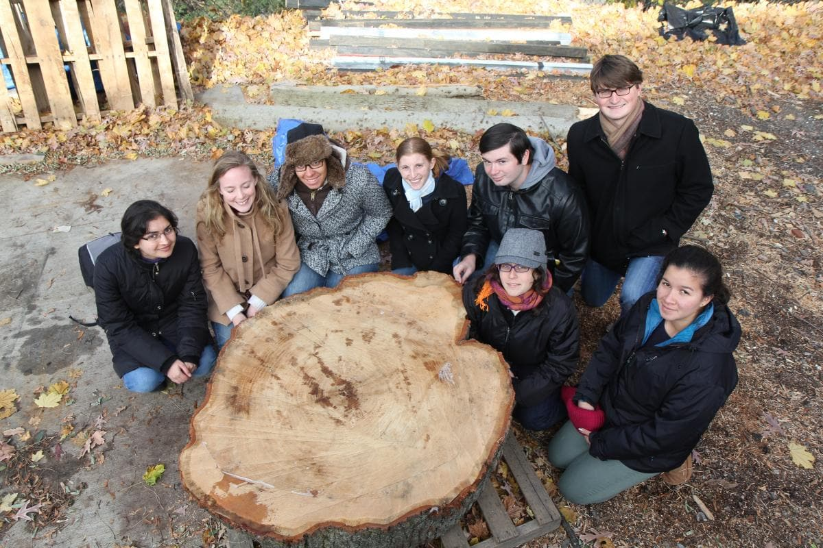 Dendrochronology students kneeling behind large cross section of a tree truck.