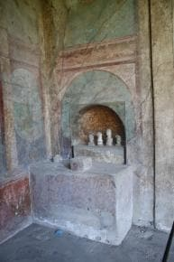 A stone altar with small figurines sitting under an archway carved into a wall