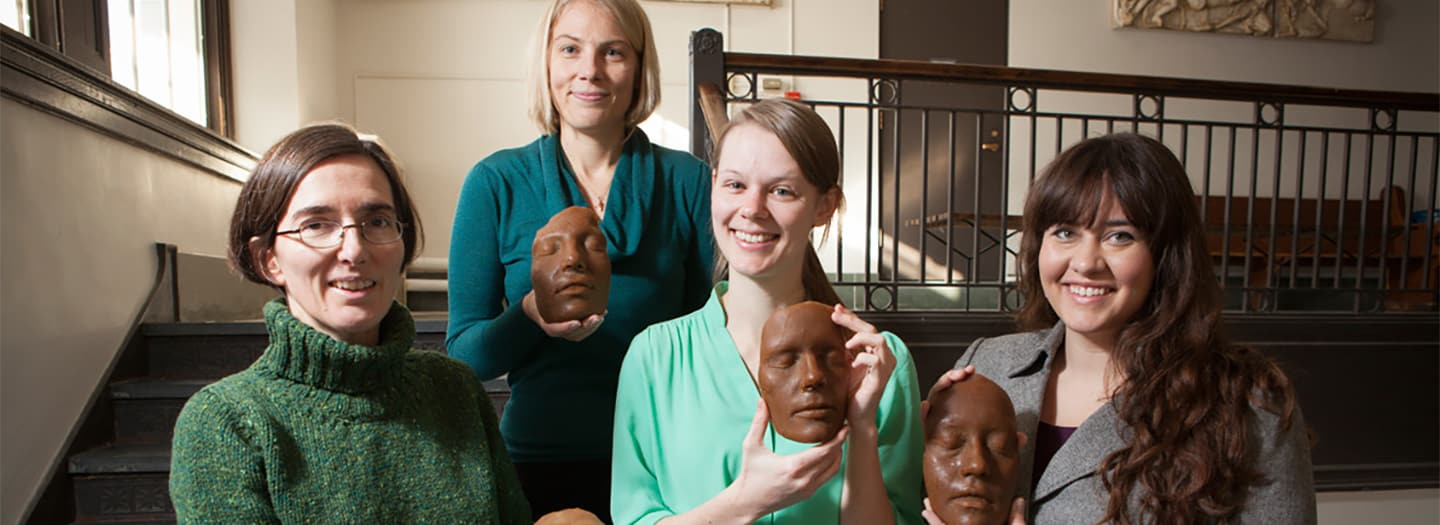 Prof. Annetta Alexandridis with former graduate students holding wax masks cast from their own faces, part of a project on Roman Imagines.